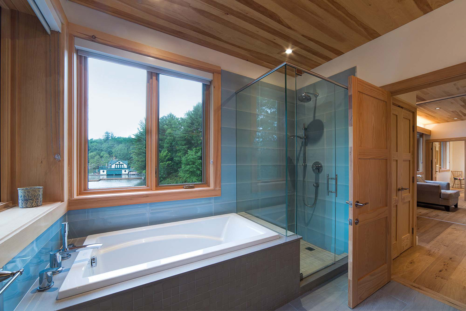 Cottage Bathroom in Muskokas with large blue tiles, glass shower enclosure and integral tub