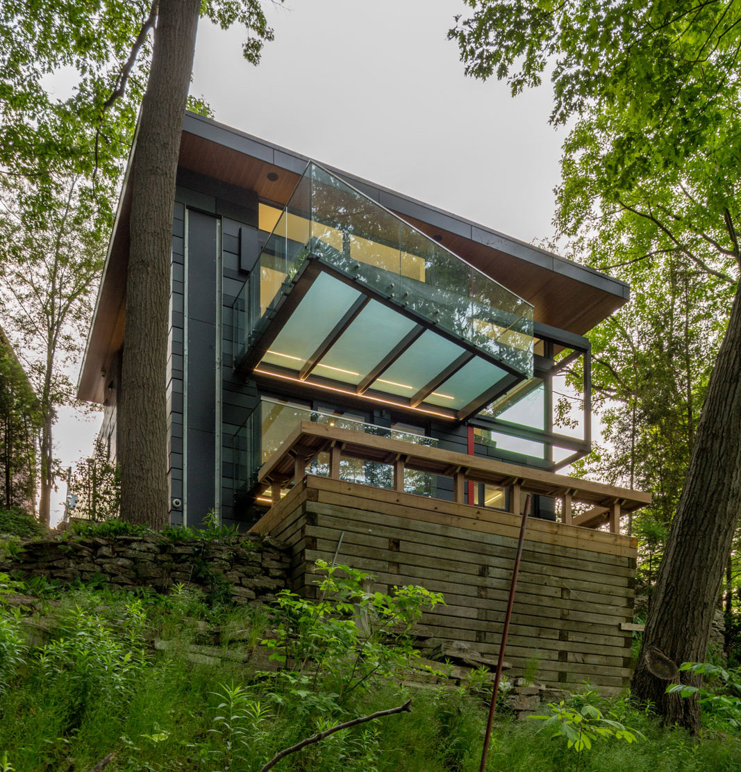 Grenadier Pond view contemporary home with translucent glass balconies, wood retaining walls and stone retaining walls integrated into natural vegetation