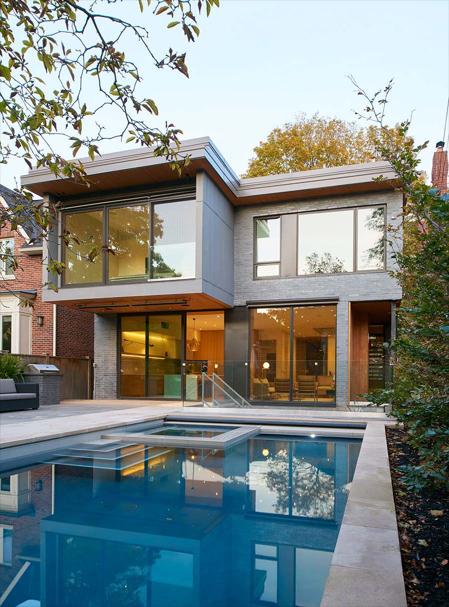 Rear yard of modern Toronto home with large cantilevered bedroom with a stone patio, large pool and integral hot tub.  Simple and elegant and modern. Designlines magazine.