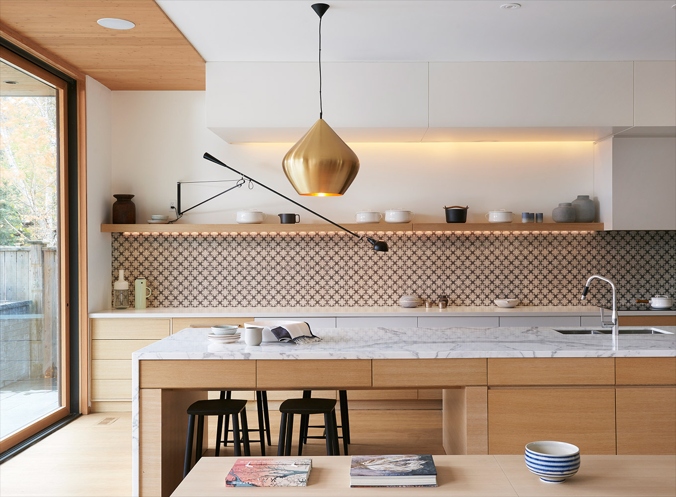 Modern kitchen with gable end marble island and counter with brass hanging light and accent tile backsplash