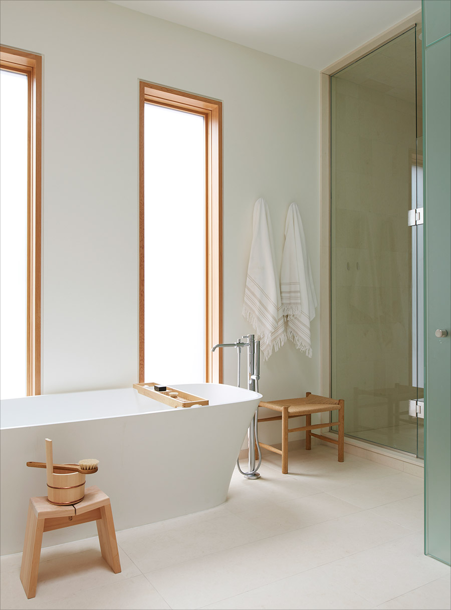Master bathroom with freestanding tub and stainless tub filler fixture and frameless glass shower enclosure