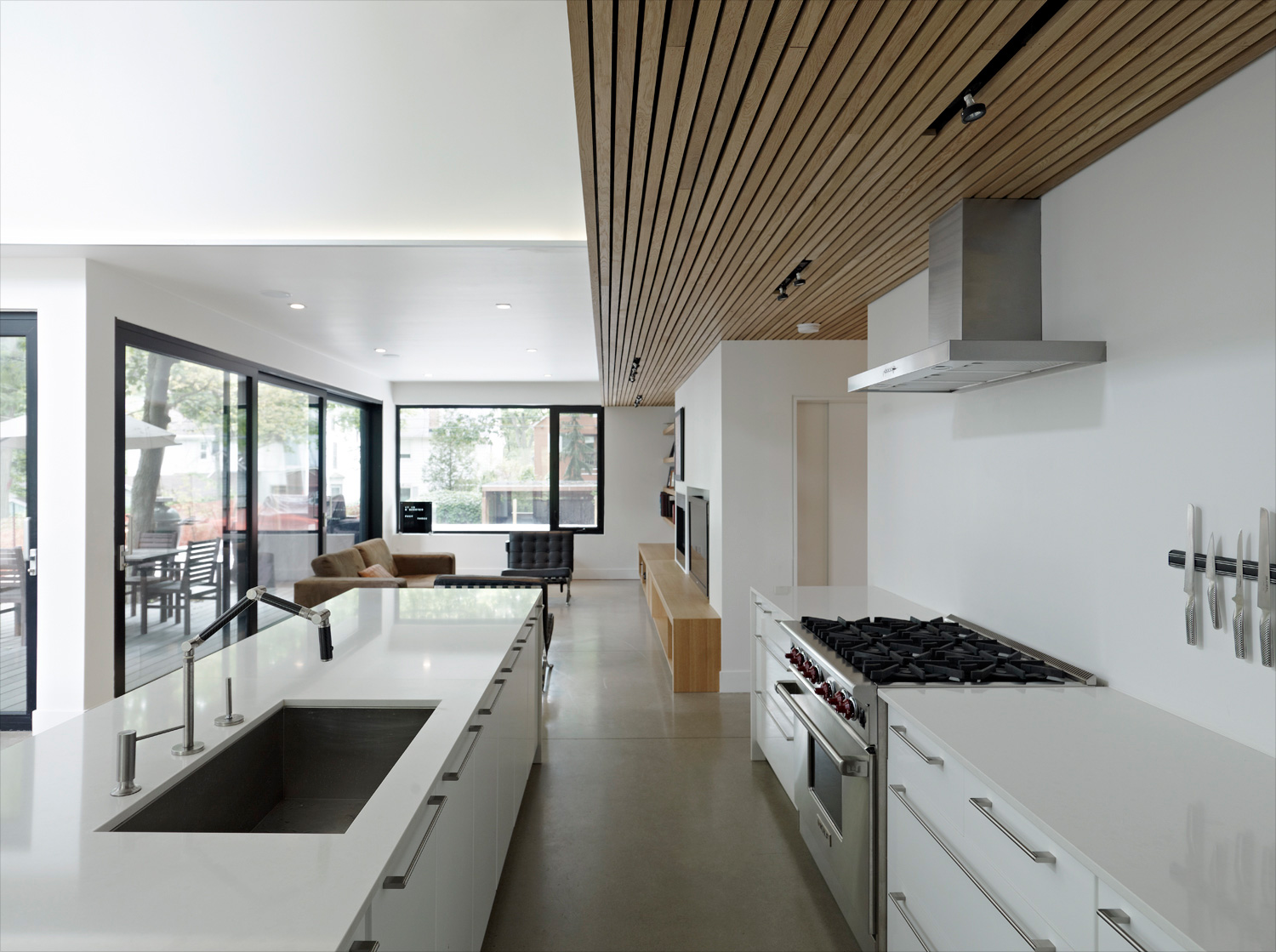 Contemporary Toronto kitchen with quartz countertops and gas range open to living room and dining room