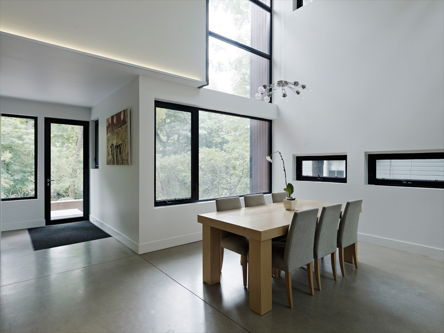 Double height dining room with modern dining room set and polished concrete floors with expansive views