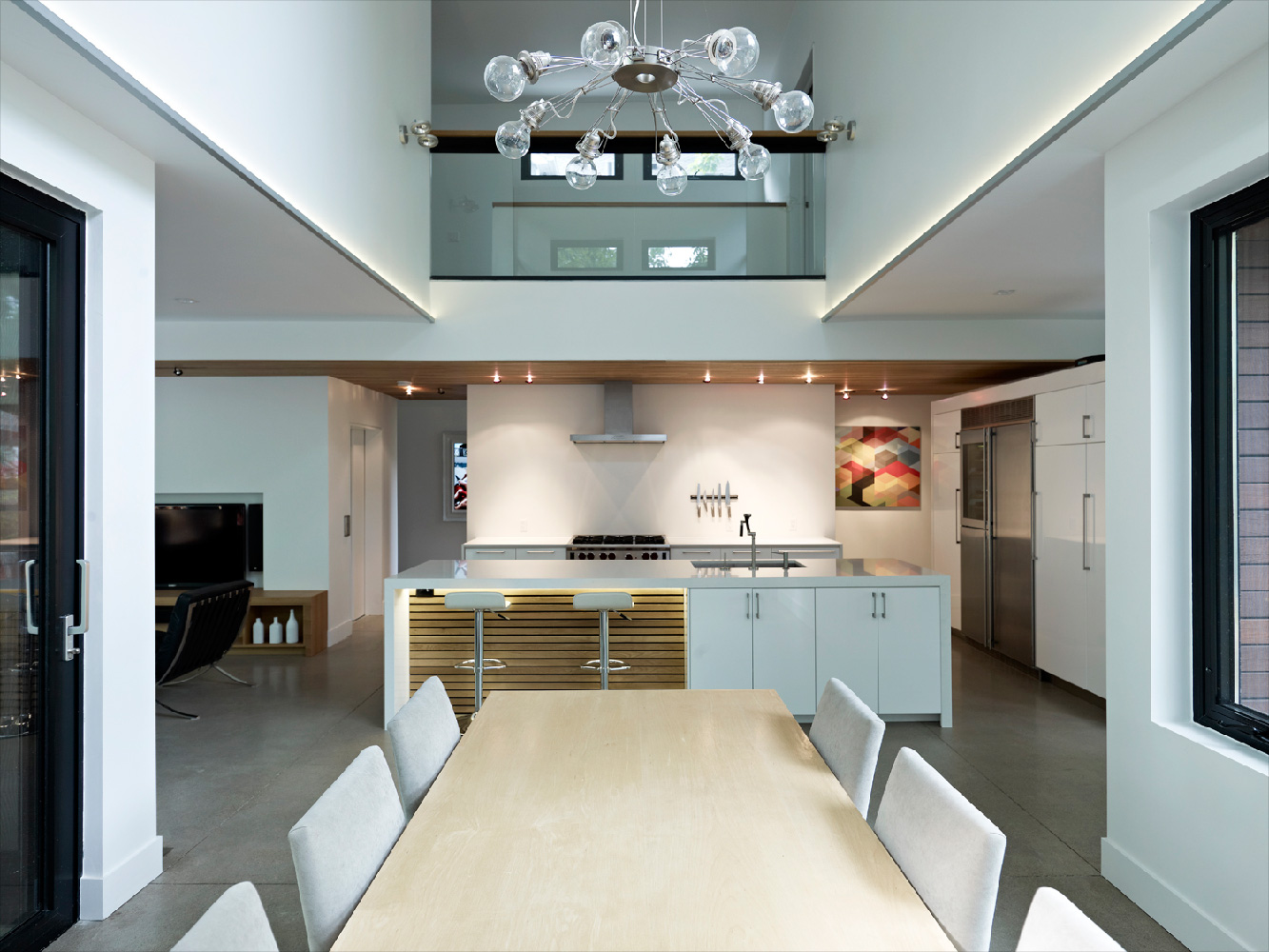 Double height modern dining room with large windows and views to front and back of house and hanging contemporary chandelier