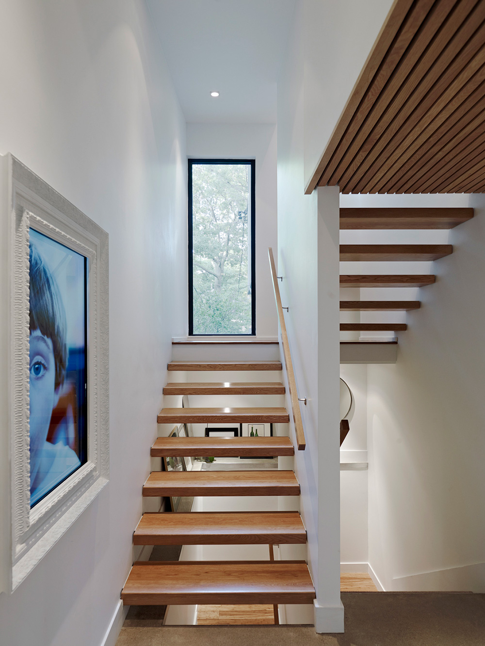 Staircase with wood tread open risers and crafted wood handrail. Large picture window on landing and a wood slat ceiling