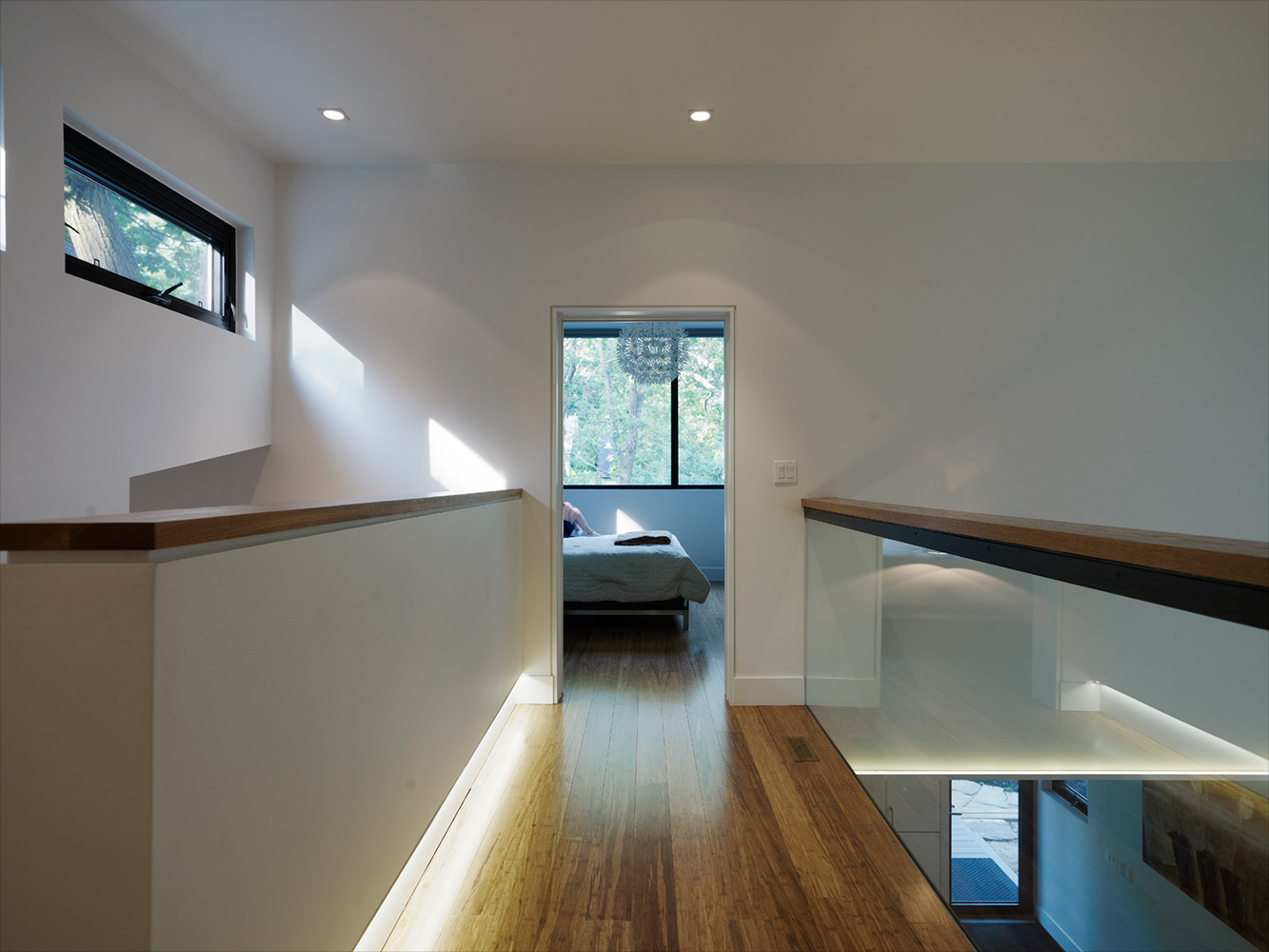 Upstairs hallway open to floor below with continuous wood handrail and glass guard with recessed lighting