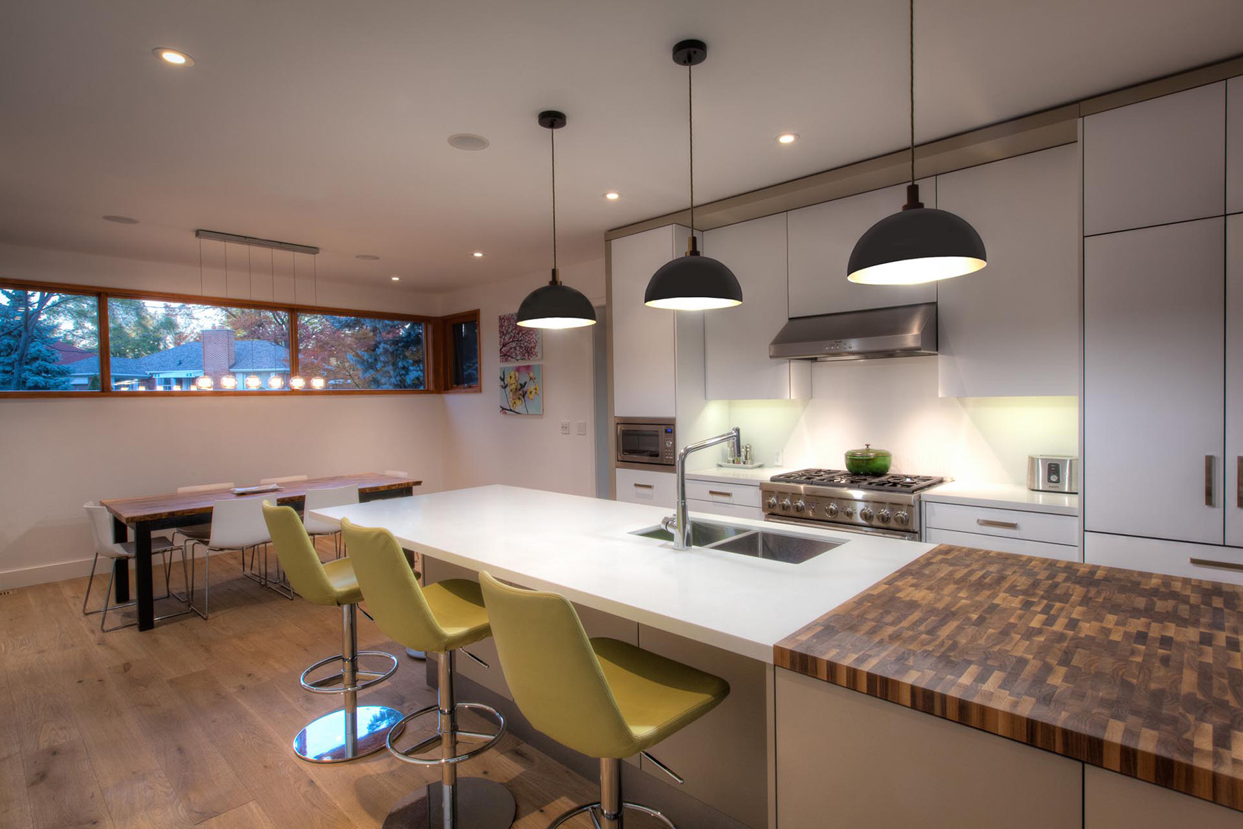 Modern kitchen design with panelled appliances and quartz island with sink and end grain butcher block