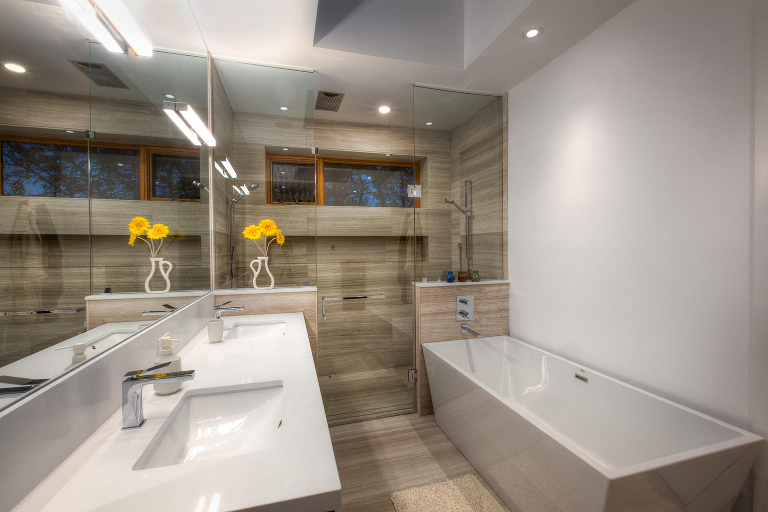 Bathroom with free standing tube and stainless steel fittings half height marble wall and glass shower enclosure