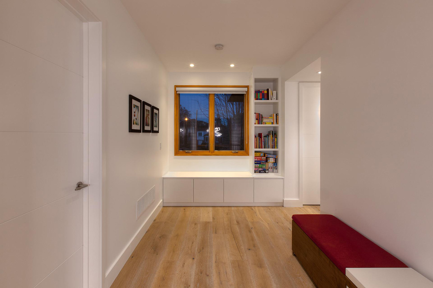 Hallway furnished with built in benches with storage and small bookshelf with pot lighting
