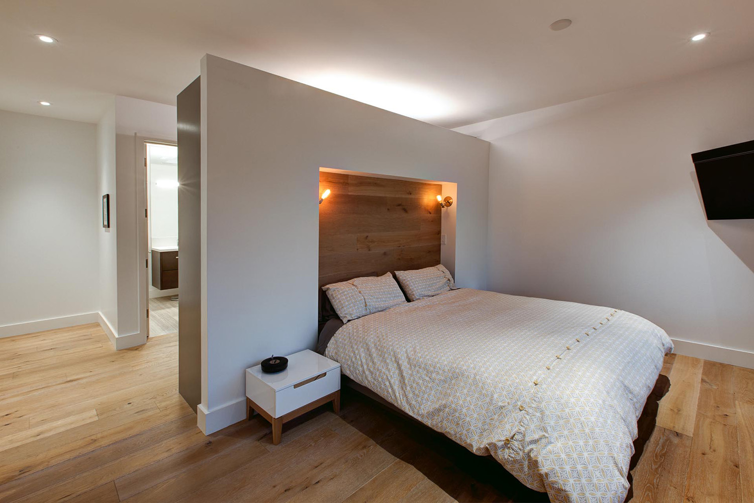 Bedroom with designed custom built headboard and lighting with ensuite washroom and wardrobe