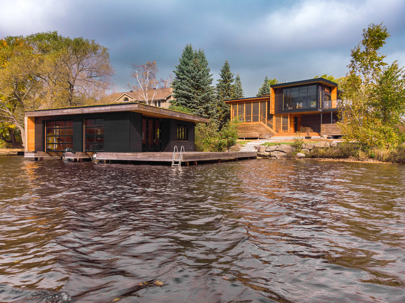 Muskoka cottage and boathouse with steel and poplar siding