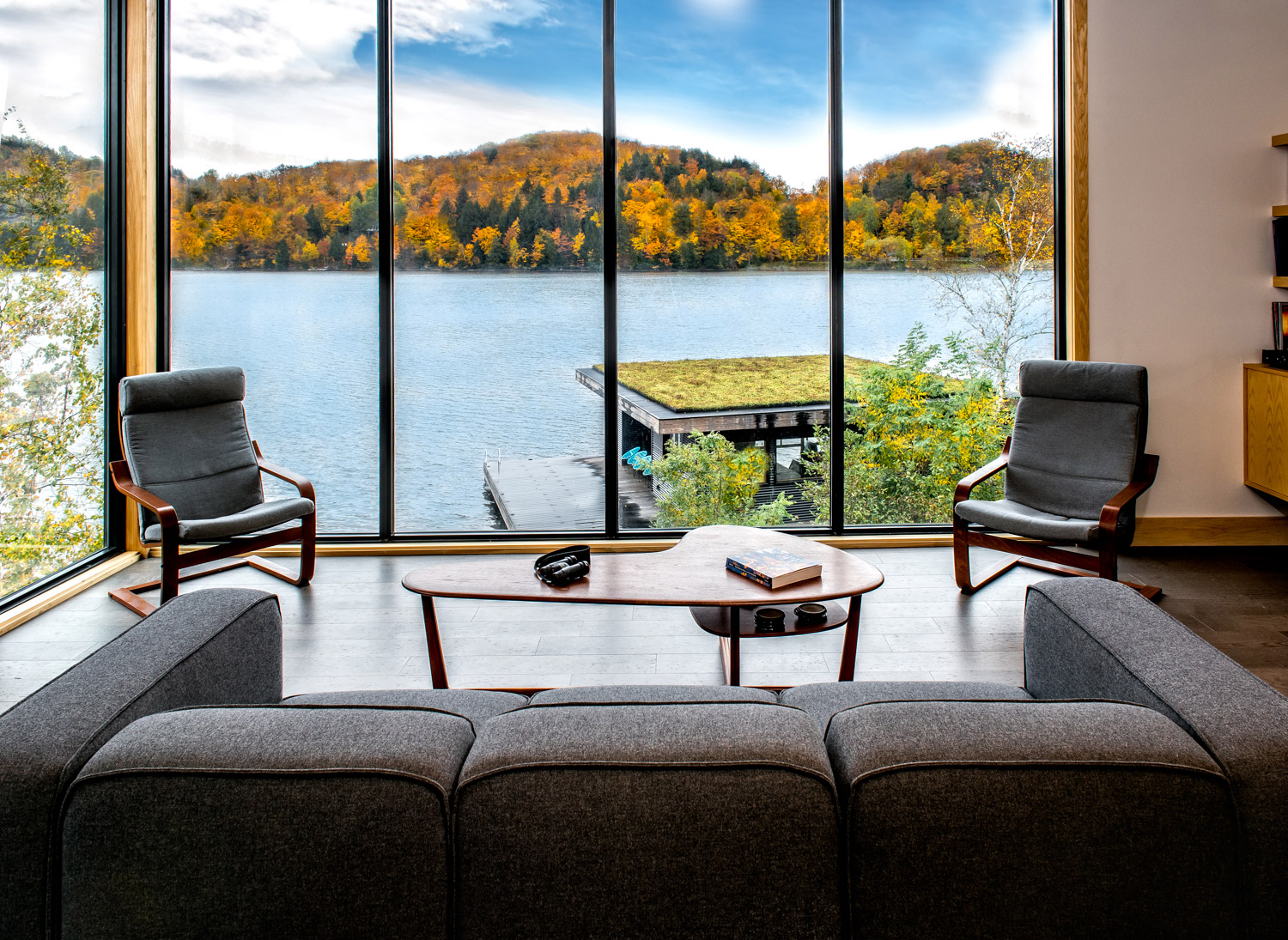 Cottage living room with floor to ceiling windows modern gray sofa and chairs and wood coffee table