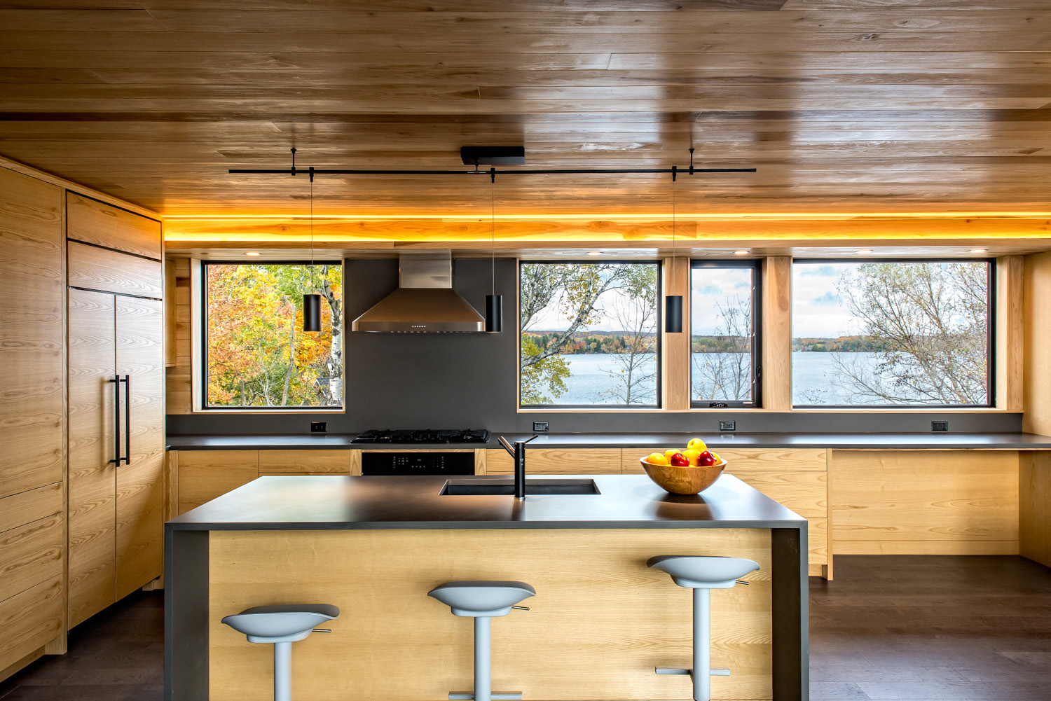Open Cottage kitchen with dark gray gable end quartz countertops, poplar cabinetry and recessed valance lighting