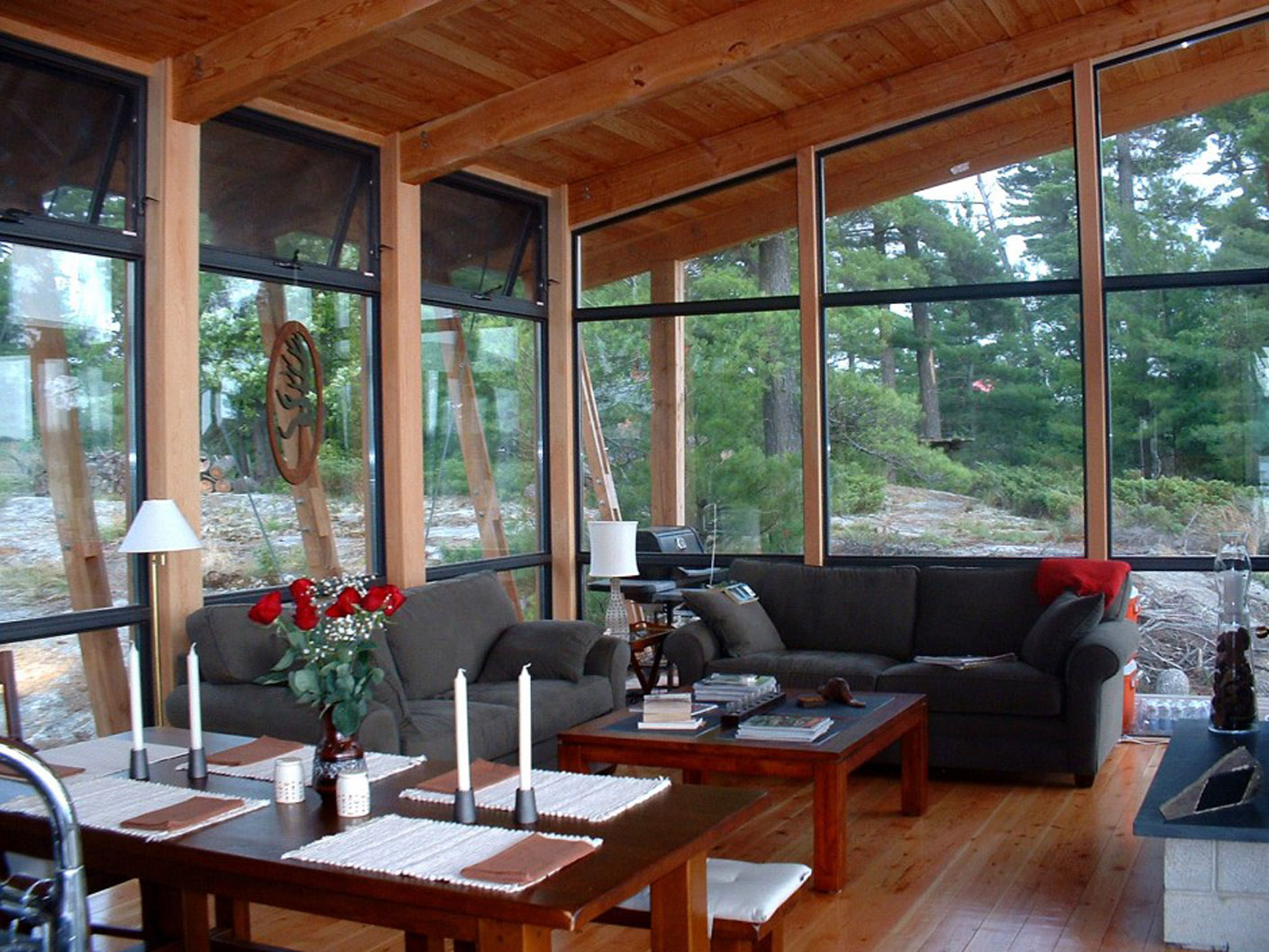 Living room in Georgian Bay cottage with large curtain walls, framed into post and beam wood cottage structure