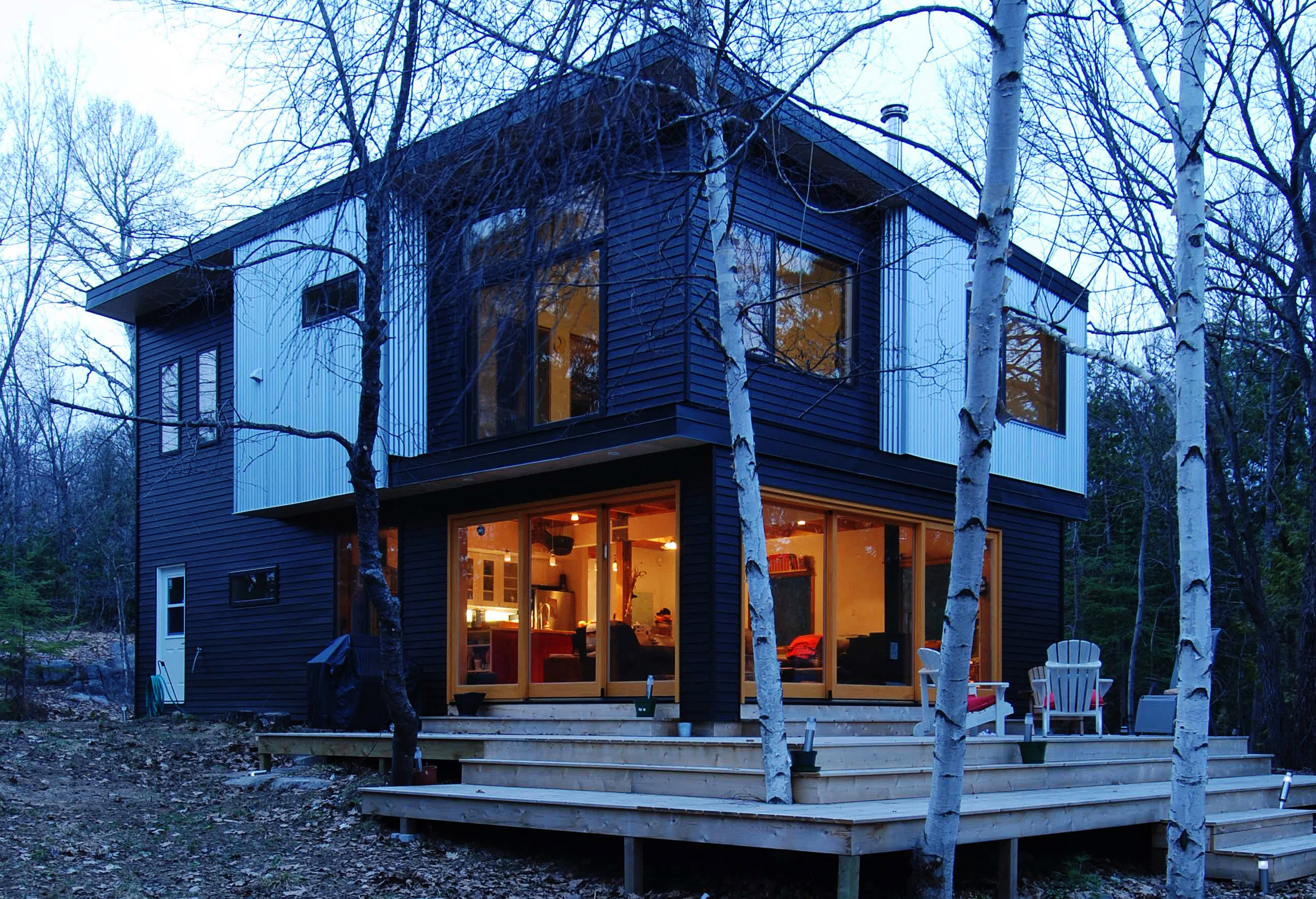 Eastern Ontario cottage with tiered deck designed around existing trees and vegetation