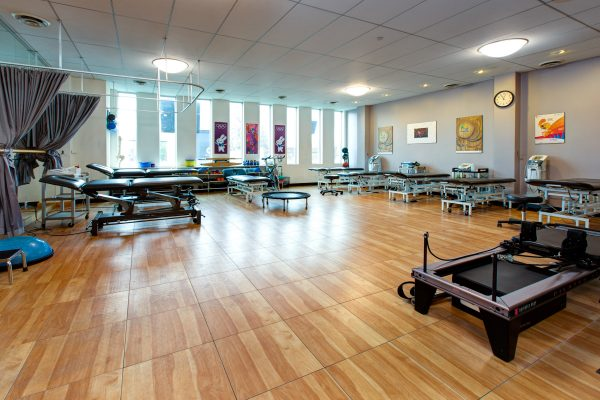 Toronto physiotherapy space, with wood flooring panels, and various medical equipment
