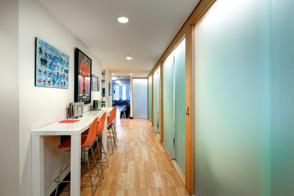 Toronto medical office hallway with frosted glass examination room doors and stool seating