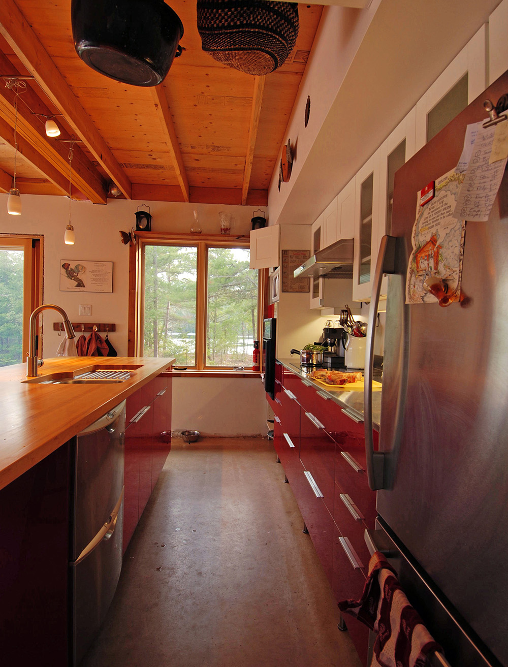 Minimalist cottage kitchen with exposed structure ceiling. Wood and Stainless steel countertops.
