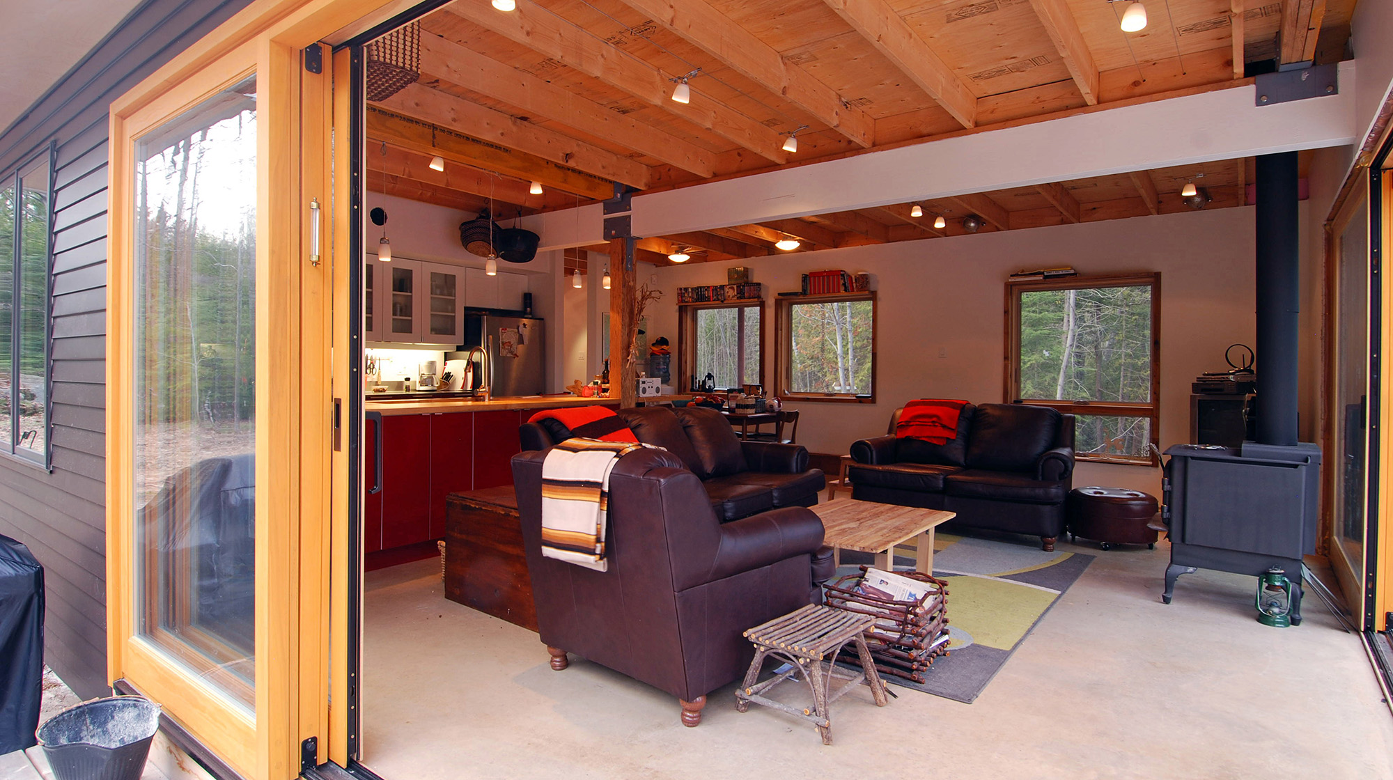 Open cottage interior with wood burning stove, polished concrete floors, exposed ceiling structure and open kitchen