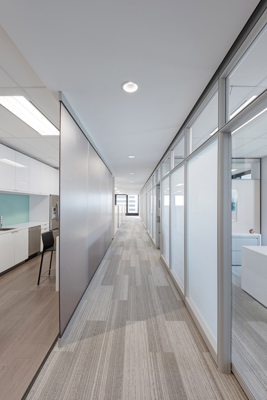 Bright office hallway with translucent glass walls to allow for natural lighting