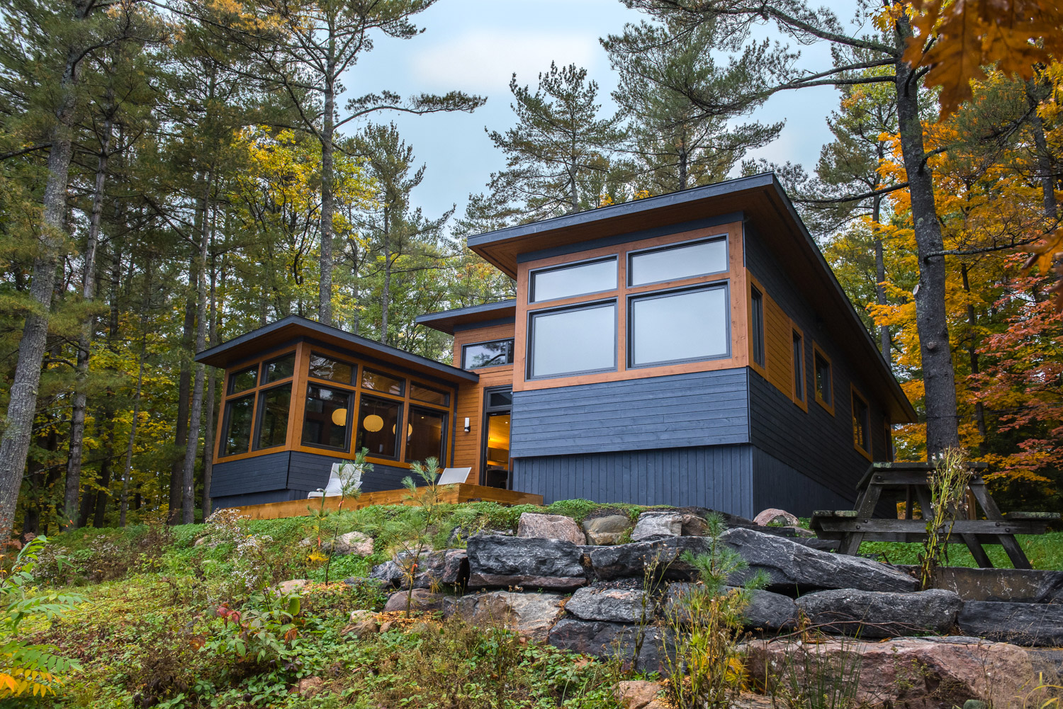 Exterior of an ontario cottage with Maibec siding and large picture windows made from two prefabricated modules