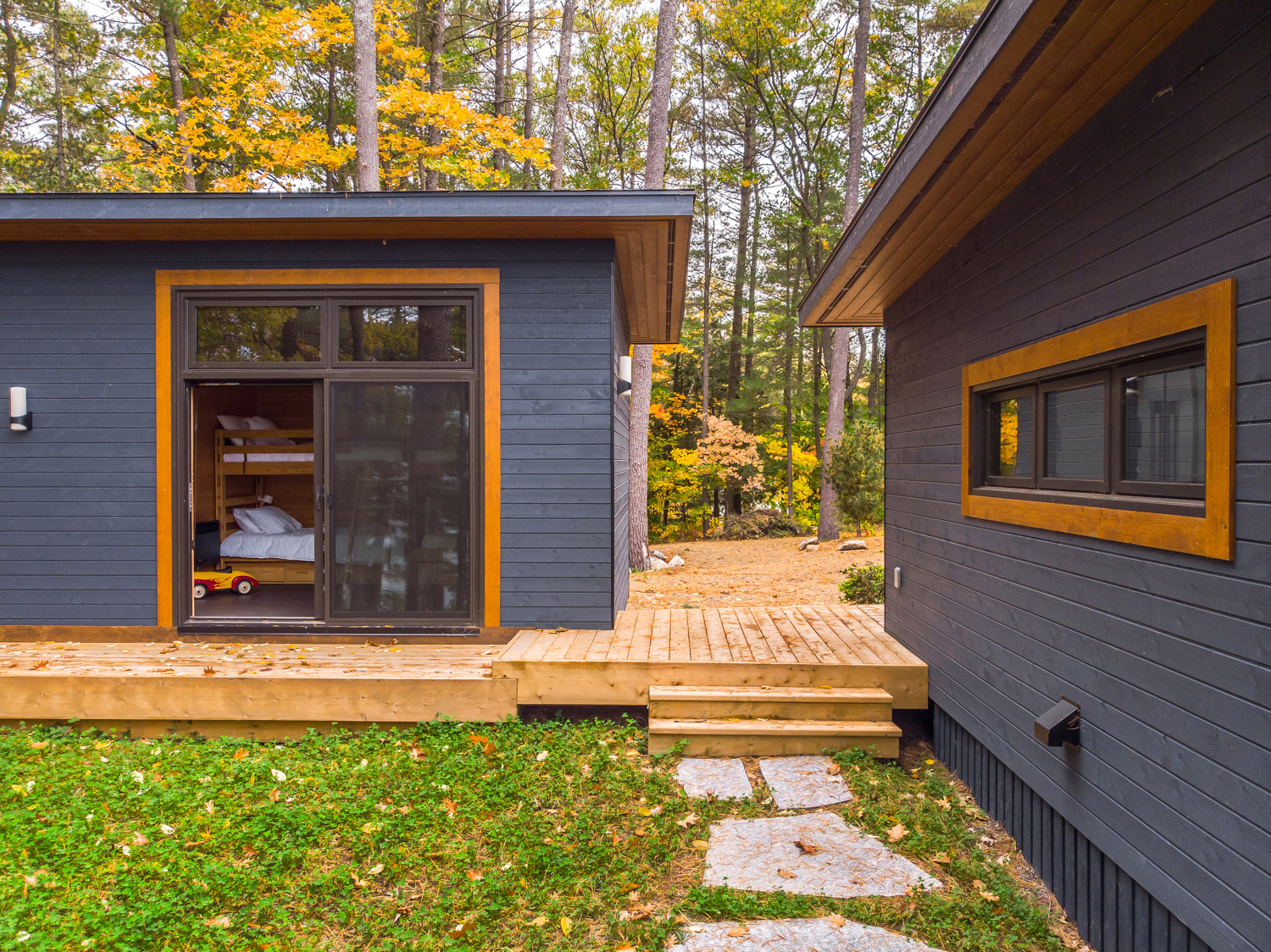 Prefabricated Canadian cottage and bunkie with connecting deck with Douglas fir soffits and wood fascia