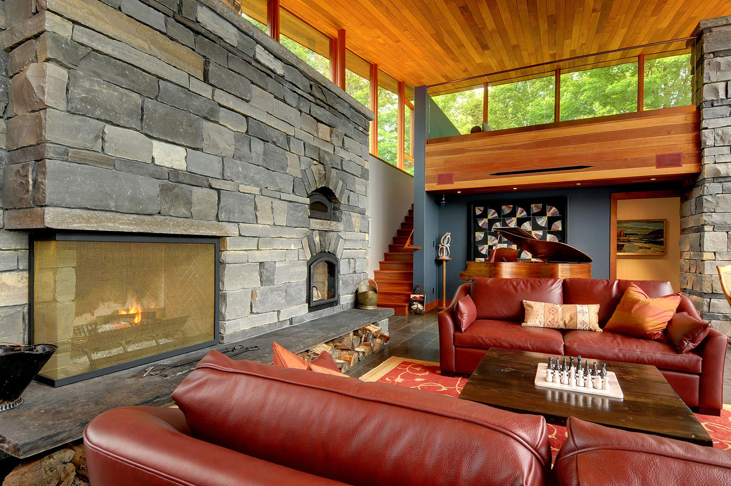 Cottage living room with wood burning stone fireplace integral wood storage and red leather sofas