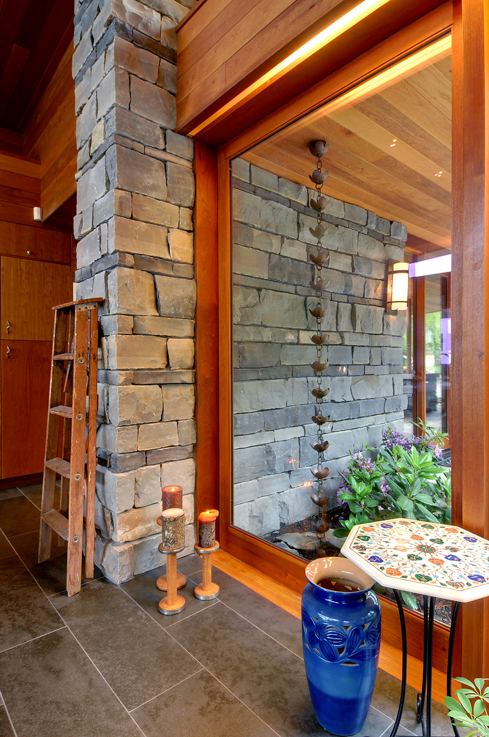 Large wood frame sliding glass door set into exposed stone wall with a recessed valance light