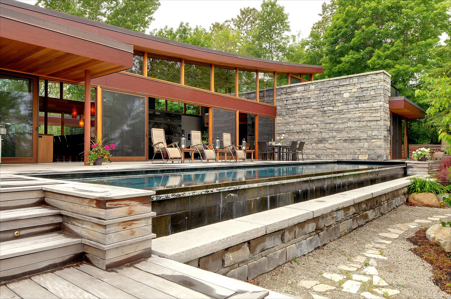 Ontario cottage outdoor deck with infinity pool set into a natural Ipe deck and large sliding doors into the cottage interior