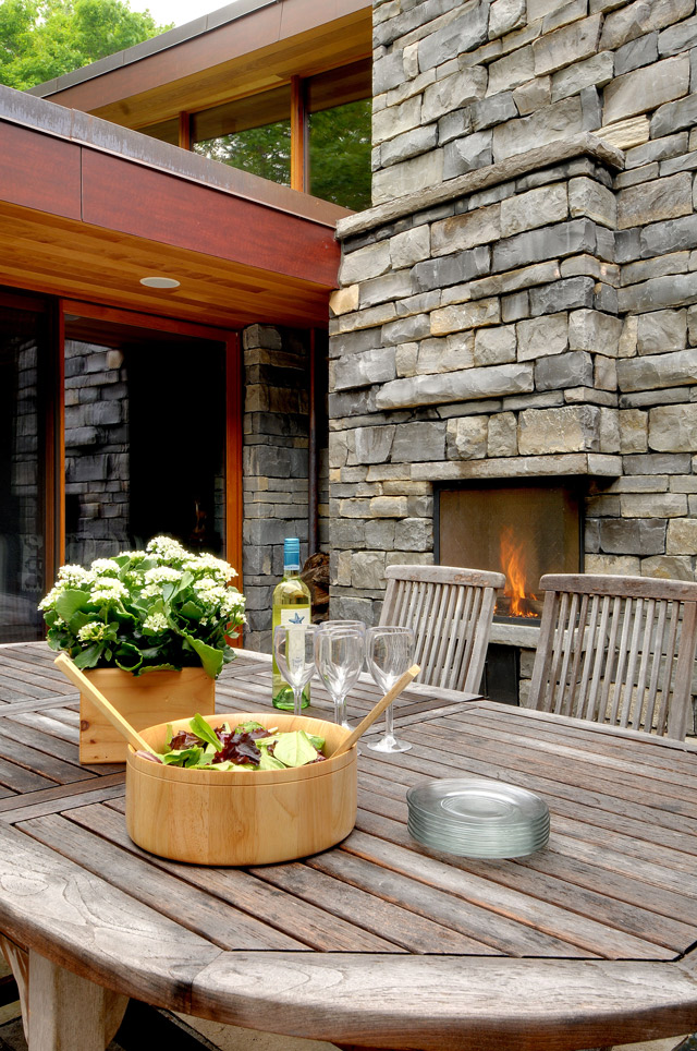 Canadian outdoor dining table with exterior stone fireplace, wood soffits and phenolic panel fascia