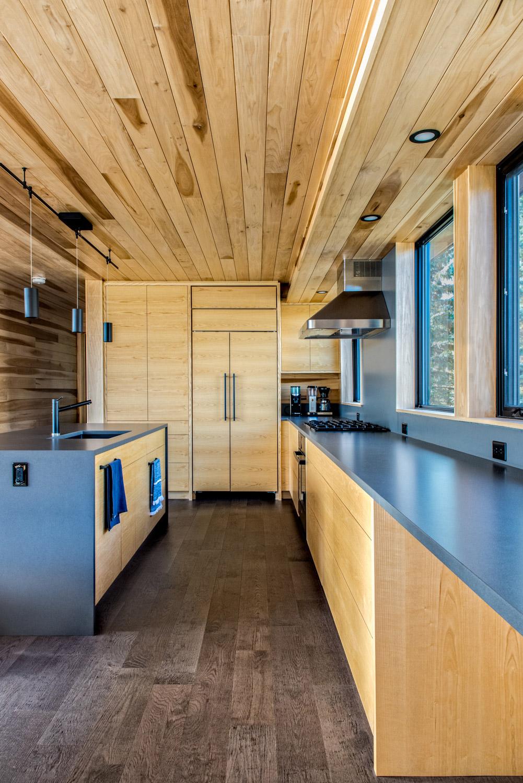 Muskoka kitchen with dark gray satin quartz countertops pendant lighting and poplar cabinetry
