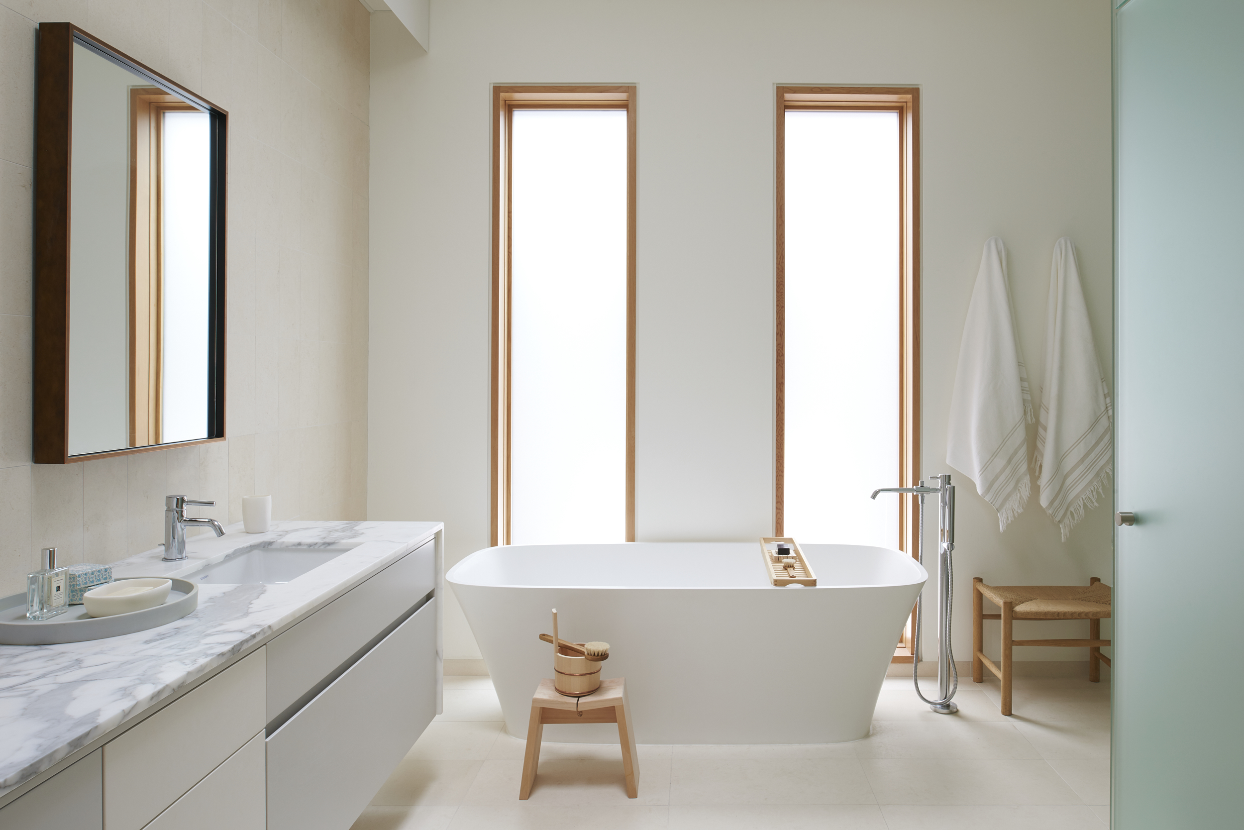 Modern Toronto beautiful architect designed master bathroom. White tile, white bathtub, wooden windows. Interior design.